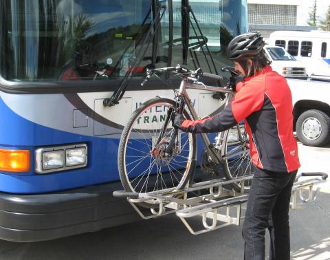 A person loading a bicycle onto the bicycle rack on the front of a bus